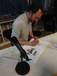 Paul Cauuet beim Signieren – statt nur Unterschrift gibt es eine kleine Zeichnung. © Helen Reményi